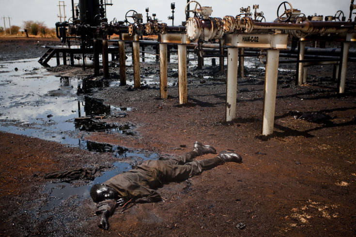 Sudan, Heglig, 2012.  A Sudan Armed Forces (SAF) soldier lies dead covered in oil next to a leaking oil facility after heavy fighting between southern Sudanese SPLA troops, after they entered the north Sudan oil town of Heglig mid April. Dominic Nahr