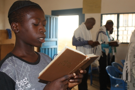In a synagogue in Nigeria, 14-year-old Kadmiel Izungu Abhor reads from a prayer book during Shabbat service. Photo by Chika Oduah