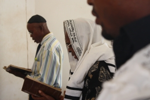 Peter Agbai (in the middle) an elder in a synagogue in Nigeria, joins men in a Shabbat service