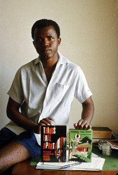 Chinua Achebe in 1960 holding copies of his 1958 novel Things Fall Apart