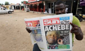 A Nigerian reads a newspaper featuring a headline on Chinua Achebe's death on 22 March. Photograph: Pius Utomi Ekpei/AFP/Getty Images