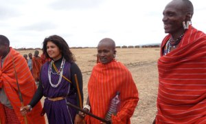 Mindy Budgor standing with a group of warriors in Maasai land