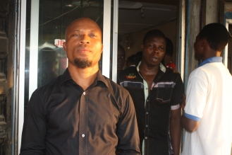 Bassey Ngehaje AKA Mr. Condom, stands in front of his shop in Eket