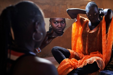 Bineta Ndiaye, 22, looks at herself in the mirror as her friend Coumba Faye, 19, fixes her hair in Faye's house in the village of Ndande. Every year, inhabitants of the village take part in a Sufi Muslim ceremony called Gamou-Ndande. The ceremony combines nights of praying and chanting as well as traditionally animist ceremonies. (Joe Penney/Reuters)