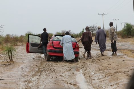 Chibok guys pushing a car out of the mud on a rainy morning.