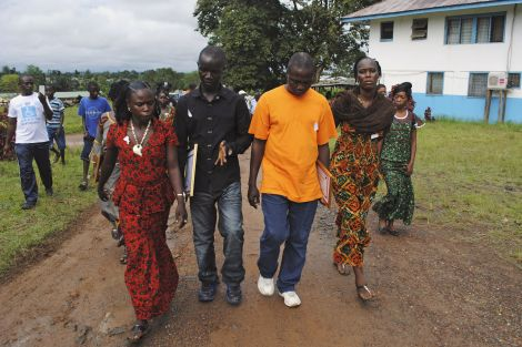 Four survivors of the Ebola outbreak, who were treated by Gorbee Logan, a Liberian doctor who says he has successfully treated Ebola patients with anti-retroviral drugs, walk at a clinic outside Monrovia October 3, 2014. REUTERS/James Giahyue