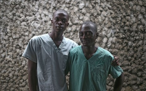 Ebola survivors Mark Jerry, 30, (R), and Zaizay Mulbah, 34, stand together before their shifts as nurse's assistants at the Doctors Without Borders (MSF), Ebola treatment center on October 12, 2014 in Paynesville, Liberia. Jerry was a money changer and Mulbah a delivery driver before they caught the disease and went to the MSF center where they recovered. MSF hired them afterwards to counsel and comfort others stricken by the disease. Ebola kills about 70 percent of the people it infects, according to the World Health Organization, but leaves survivors immune to the strain that sickened them. (Photo by John Moore/Getty Images)