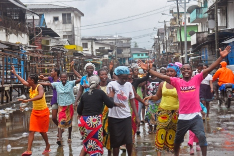 People celebrate Saturday on the streets of the West Point slum area in Monrovia, Liberia, after the quarantine was lifted. The slum was once sealed off by security forces in August 2014 in an attempt to control the Ebola outbreak. (Abbas Dulleh/AP)