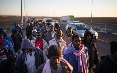 BEER SHEVA, ISRAEL - DECEMBER 16: (ISRAEL OUT) African migrants walk on a highway as they try to walk to Jerusalem in protest after abandoning a detention facility in the southern Israeli desert on December 16, 2013 near Beer Sheva, Israel. Over 100 African migrants abandoned the 'open' Israeli detention center, which opened last week, to march to Jerusalem to protest a law allowing authorities to keep them in open-ended detention until the resolution of their asylum requests are granted or they are deported or volunteered to leave the country. (Photo by Uriel Sinai/Getty Images)