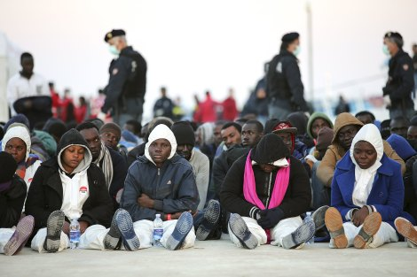 Migrants rest after they disembarked in the Sicilian harbour of Augusta, April 16, 2015. Italian police arrested 15 African men suspected of throwing about a dozen Christians from a migrant boat in the Mediterranean on Thursday, as the crisis off southern Italy intensified. REUTERS/Antonio Parrinello
