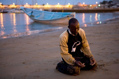 July 1, 2008: A man offer prayers of thanks after arriving at a beach on Spain's Canary island of Gran CanariaBorja Suarez/Reuters Mediterranean migrants