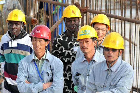 Senegalese and Chinese workers observe a ceremony at the national theater construction site financed by China on February 14, 2009 in Dakar, during a visit by Chinese president Hu Jintao and Senegalese president Abdoulaye Wade. AFP Photo / SEYLLOU_24 FEB 2013