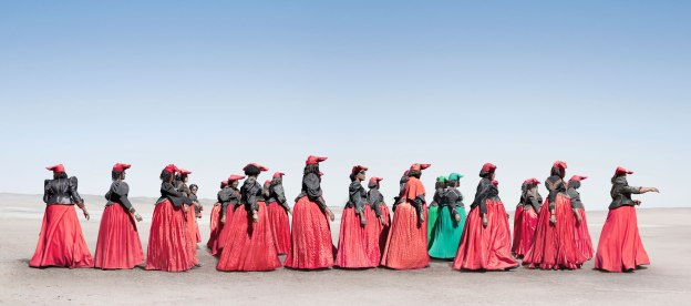 A photo graph of modern-day Herero women. Herero women marching. In 2011 Jim Naughten spent four months photographing the Herero tribe of Namibia. The London-based photographer drove thousands of miles through the desert, meeting and negotiating with people, camping and continuously cleaning the dust out of his camera equipment. Photo: Jim Naughten