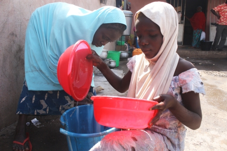11-year old Hauwa Marshall gathers water, Fatimatu, 14, washes dishes behind her. They were orphaned when Boko Haram fighters killed their father a few weeks ago. Now, they live in his refugee camp in Yola in northeastern Nigeria. January 17. Photo by Chika Oduah