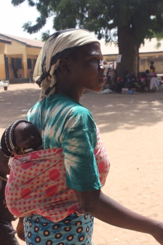 Rose, 25, carries 28-day-old Ibrahim on her back. The baby boy's twin brother was killed by Boko Haram insurgents the day he was born. The insurgents also killed his mother the same day. Yola, northeasern Nigeria. January 17, 2015. Photo by Chika Oduah