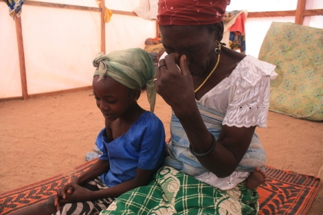 Jummai Joshua, 8-year-old orphan, prayers with her grandmother inside the tent they share in a refugee camp in Yola, northeastern Nigeria. She and her grandmother fled their village in January when Boko Haram fighters attacked, killing her father. January 17, 2015. Photo by Chika Oduah