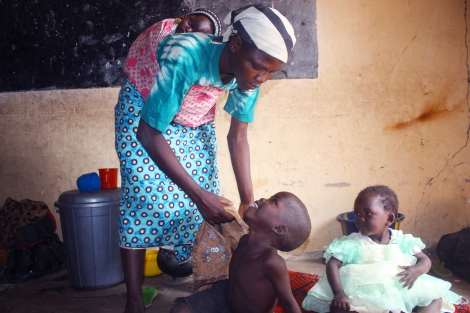 5 year old orphan, Moses Luka, smiles at his aunt as she dresses him in a shirt, as his cousin Ladi looks on. Baby orphan Ibrahim rests on his aunt's back. They arrived in the refugee camp a day ago. January 17, 2015. Photo by Chika Oduah.
