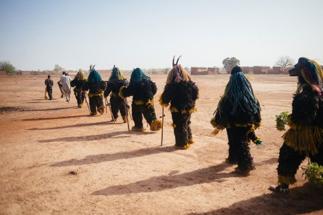 Fibre masks wearers from Tcheriba village march towards the Regional Stadium of Dedougou. Photo by Jacob Balzani Loov
