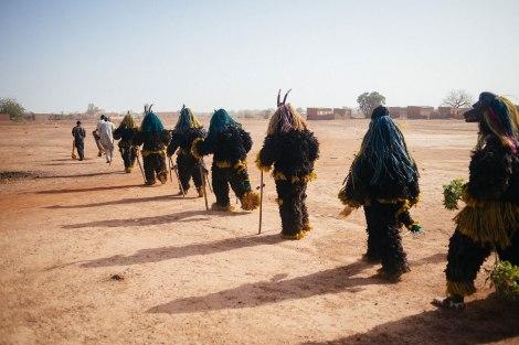 Fibre masks wearers from Tcheriba village march towards the Regional Stadium of Dedougou. Photo by Jacob Balzani Loov
