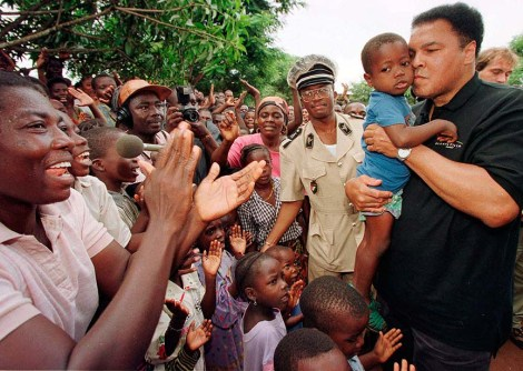 Former heavyweight boxing champion Muhammad Ali kisses a Liberian orphan while residents cheer Ali's arrival at an orphanage for Liberian refugees in San Pedro, Ivory Coast. Ali and his entourage came on a goodwill visit to donate food, wheelchairs, and medicine after receiving a letter asking for help from the mission's organizer Sister M. Sponsa Beltran. Aug. 20, 1997 (AP Photo/David Guttenfelder)