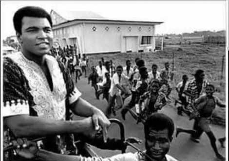 A swarm of Nigerian boys run after Muhammad Ali. Lagos, 1964