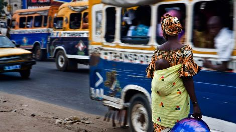A woman stands on a busy street in Dakar, Senegal. Photo by Edgar de Bono