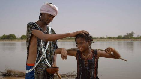 A man playfully pats the head of a Fulani child. A scene from the film.